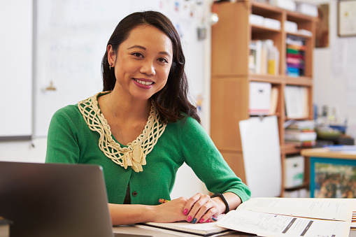 Portrait of female Asian teacher at her desk